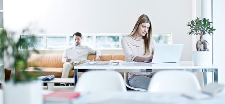 Žena sjedi za stolom s prijenosnim računalom, muškarac straga na narančastoj sofi, biljke, bilježnice, bijele stolice i prozor