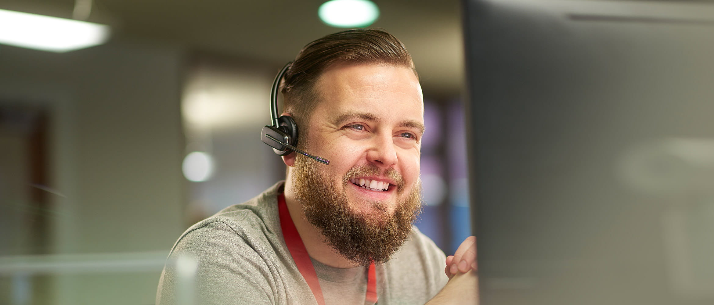 Smiling man talking on a hands free headset and looking at a computer screen