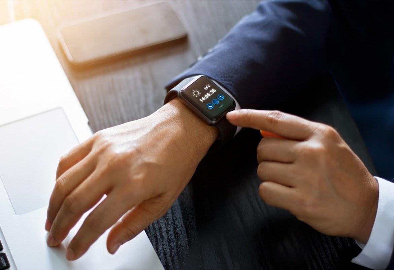 Muškarac u jakni koristi nosivu tehnologiju u obliku pametnog sata na radnom mjestu budućnosti