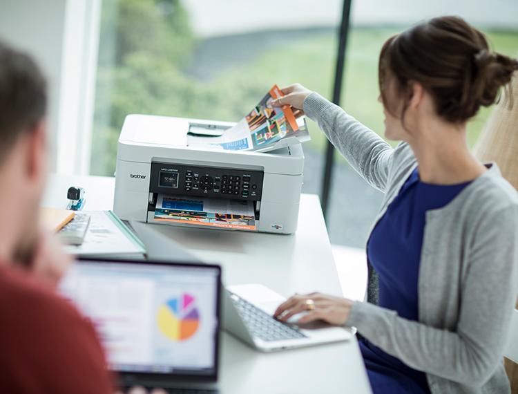 Žena u plavoj majici i sivoj jakni pored pisača u kućnom uredu